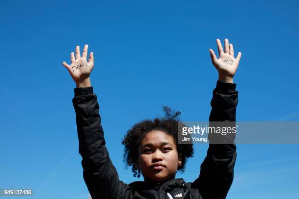 A student holds up her hands while taking part in National School Walkout Day to protest school violence on April 20 2018 in Chicago Illinois...