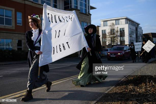 Student Hope Williams leads the group while they recreate a suffragette protest march through the town centre at Royal Holloway University of London...