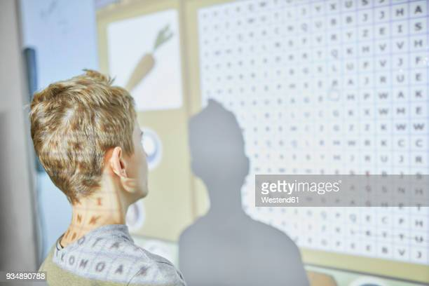 Student in class at interactive whiteboard