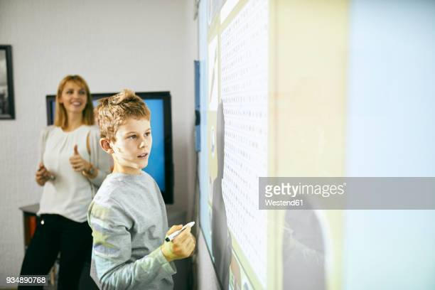 Student in class at interactive whiteboard with teacher in background