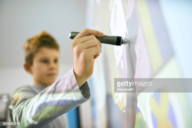 Student in class using digitized pen at interactive whiteboard