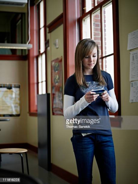 Student in classroom texting on smart phone