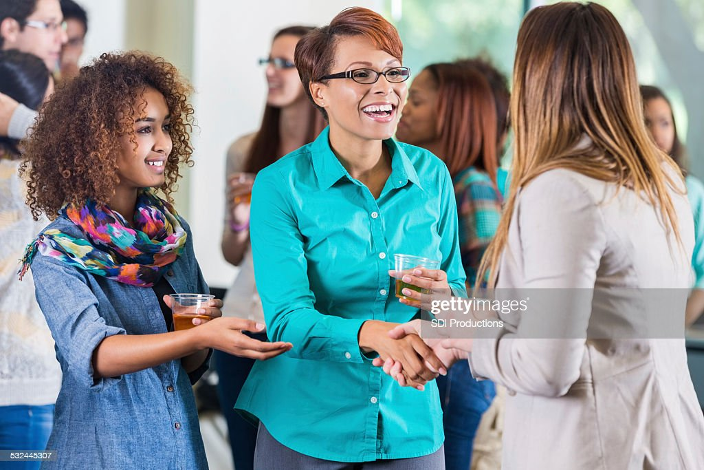 Student introducing parent to teacher during meet and greet party : Stock Photo