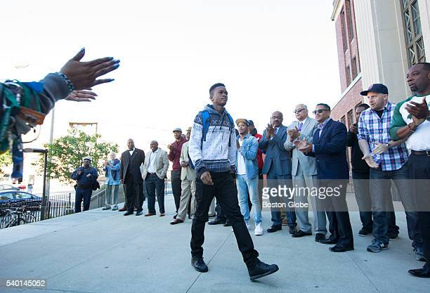 Student Jason Moffant was greeted by men of color from Boston and surrounding communities as he arrived at Jeremiah Burke High School on Monday...