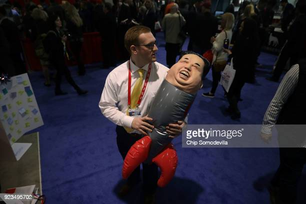 Student John Graber poses for a photograph with a inflateable rocket with a Kim Jongun mask at the Secure America Now booth in the Conservative...