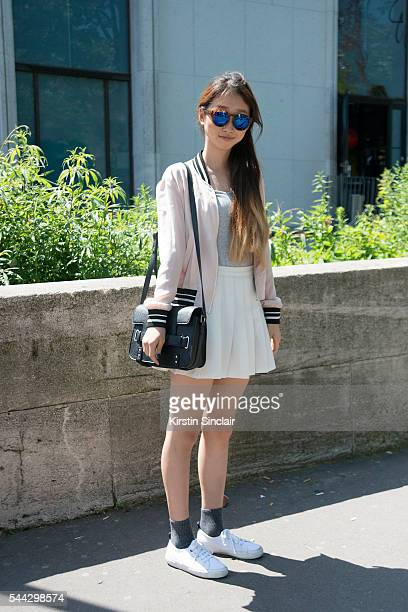 Student Joy Sin wears Forever 21 bag and sunglasses Bershka jacket Super R shoes and a Zara skirt on day 2 of Paris Collections Men on June 23 2016...