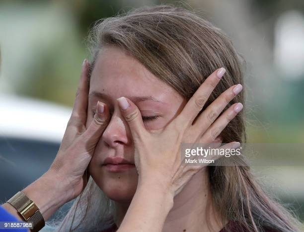 Student Kelsey Friend gets help wiping away her tears after recounting her story about yesterday's mass shooting at the Marjory Stoneman Douglas High...
