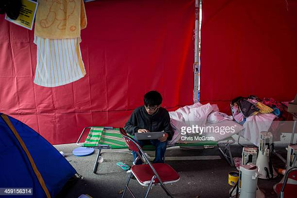 Student leader and pro-democracy activist Joshua Wong works on his laptop in a tent on the road outside Citic Tower on November 18, 2014 in Hong...