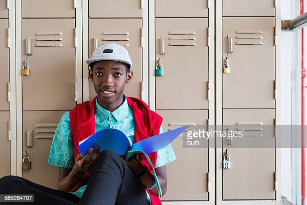 Student leaning against lockers, looking up from textbook