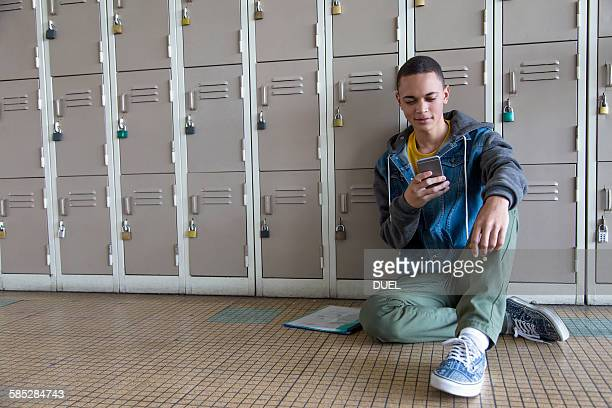 Student leaning against lockers, using smartphone