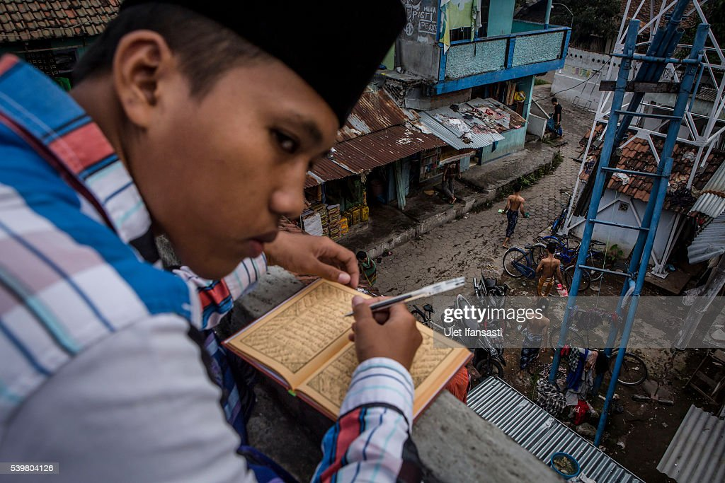 A student learns Islamic scriptures on the roof top in the islamic boarding school Lirboyo during the holy month of Ramadan on June 9, 2016 in Kediri, East Java, Indonesia. The Islamic boarding school, Lirboyo, was founded by KH Abdul Karim in 1910, and known to be one of the largest traditional 'Pesantren' in Indonesia, with around 17,000 students in Kediri, East Java. Students at the Pesantren, also known as 'Santri', are separated from their families and spend their days studying Islamic scriptures, reading the Quran and learning Arabic in addition to other activities which begins with the morning prayer at 4am till midnight.