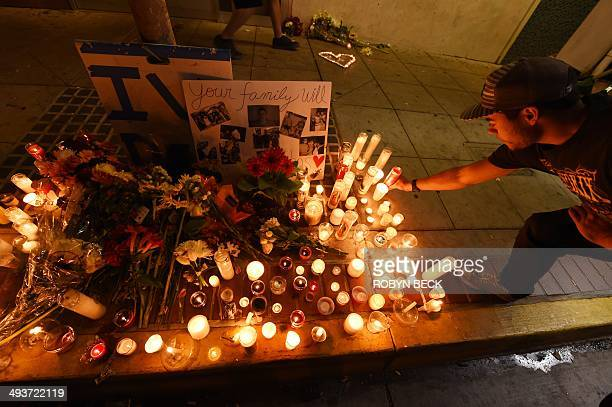 A student lights a candle at a makeshift memorial outside the IV Deli Mart where one of the victims of a killing spree was shot and killed near the...