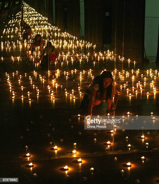 A student lights candles in front of a mirror during a performance art show to commemorate the Nanjing Massacre at Guangzhou Academy of Fine Art on...