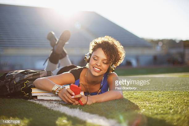 Student listening to mp3 player in grass