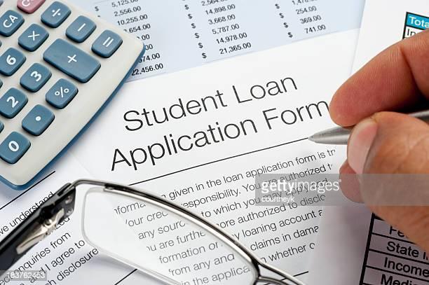 student loan application form with pen, calculator and writing h - college application stock photos and pictures