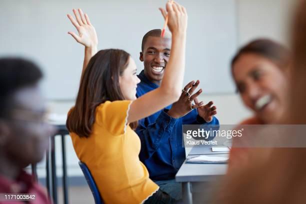 student looking friend gesturing with arms raised - s'impliquer à fond photos et images de collection