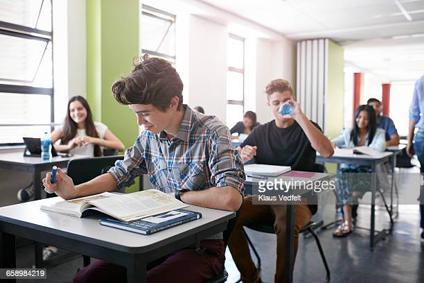 Student looking in book in classroom