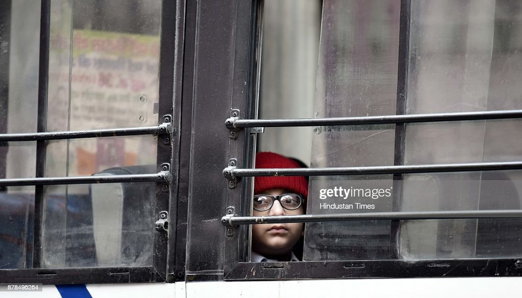 A student looking out of the window of a school bus on a cold winter morning on November 24 2017 in New Delhi India North India is under the spell of.