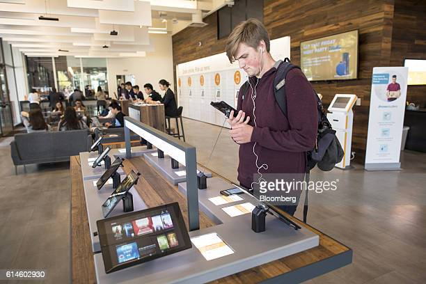 A student looks at an Amazoncom mobile device at an Amazoncom Inc kiosk on the University of California Berkeley campus in Berkeley California US on...