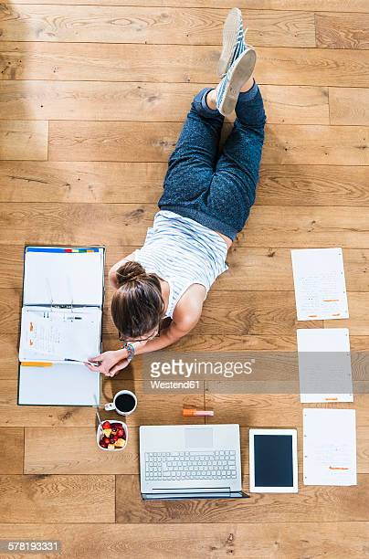 Student lying on wooden floor surrounded by papers, laptop, digital tablet, file folder, coffee and fruit bowl