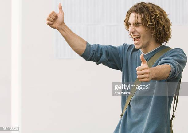 student making thumbs up sign and shouting with joy, in front of results on wall - baccalaureat stock pictures, royalty-free photos & images
