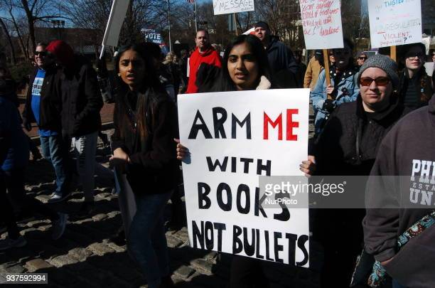 A student marches with a sign demanding greater support for education than for guns in American Culture during March For Our Lives Philadelphia on...