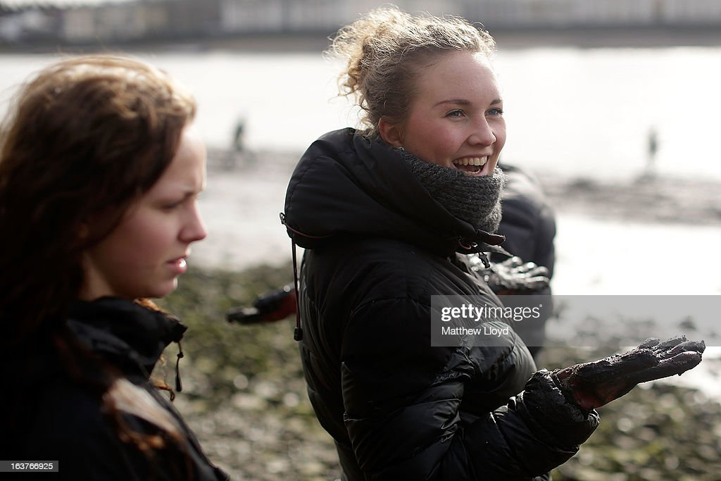 Student Matilde Gydesen from Denmark reacts after removing a mud covered tyre from the banks of the Thames on the Isle of Dogs on March 15, 2013 in London, England. The Thames21 charity leads volunteers in deep cleans of some of the Thames' most polluted and littered areas, using the annual low tides to reach areas normally impossible to access.