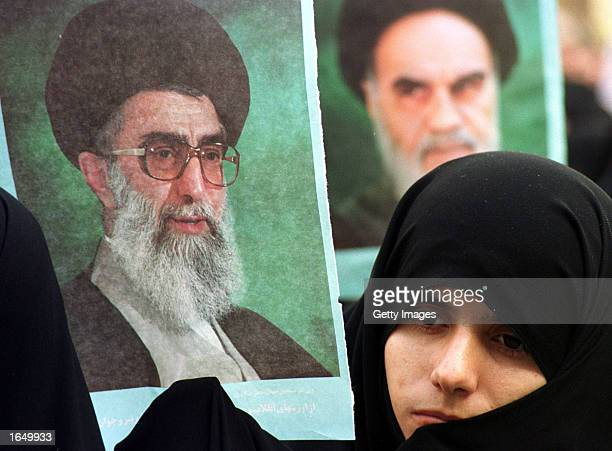 Student member of the Basij holds a picture of Iran's supreme leader, Ayatollah Ali Khamenei , next to a photo of Ayatollah Khomeini, founder of the...