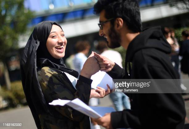 Student Mona Abou Dahech fist bumps a fellow student after opening her results on GCSE results day at the City of London Academy, Hackney on August...