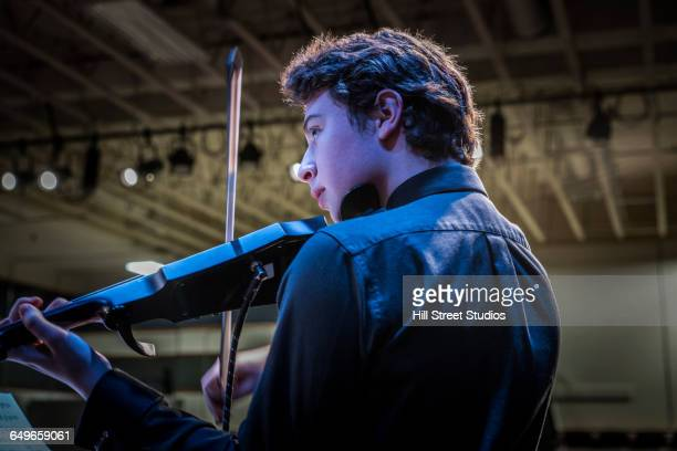 Student musician playing violin on stage