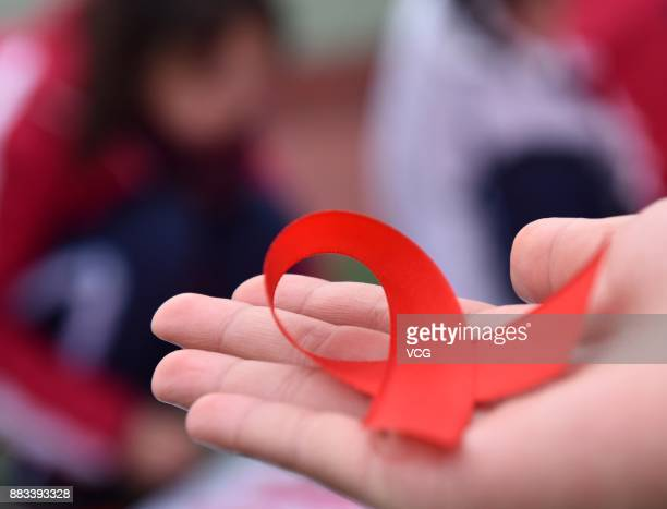 A student of Chaohu No2 Middle School shows handmade red ribbons on November 30 2017 in Chaohu Anhui Province of China Chaohu No2 Middle School...