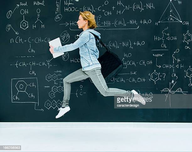 Student of chemistry running by blackboard
