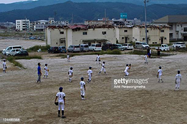 Student of Takada Elementary school attend a baseball game next to a devasted area prior to the sixth month anniversary of the March 11 earthquake...