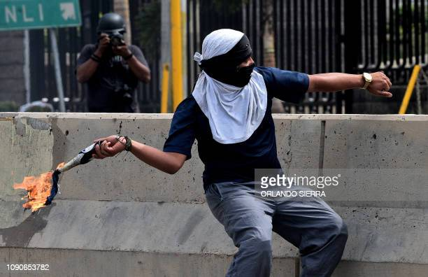 A student of the Autonomous National University of Honduras throws a Molotov cocktail at riot police during a protest demanding the resignation of...