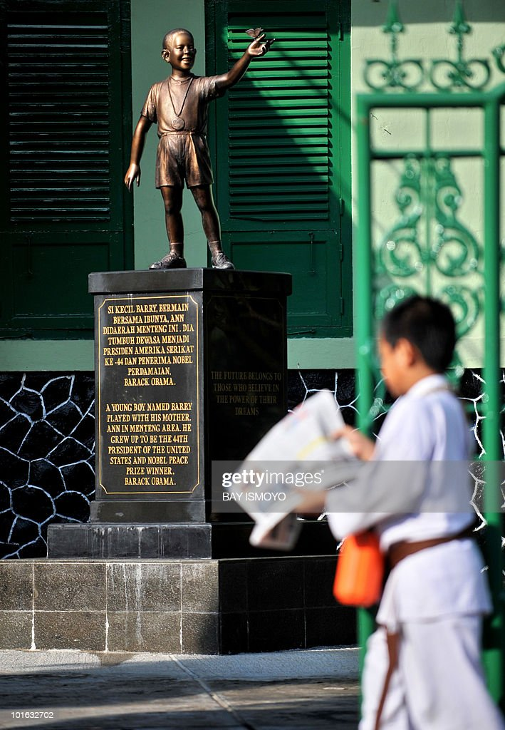 A student of the Menteng One primary school, where US President Barack Obama attended as a young boy in the late 1960s, carries a newspaper close to a statue depicting Obama as a young boy in Jakarta on June 5, 2010. Faced with mounting challenges at home, Obama will soon have to choose between jamming foreign trips onto this year's tightening schedule or neglecting key US partners. Obama, who traveled overseas more than any other president in his first year, called off a visit to Australia and Indonesia for the second time to focus on curbing a major oil leak in the Gulf of Mexico. AFP PHOTO / Bay ISMOYO