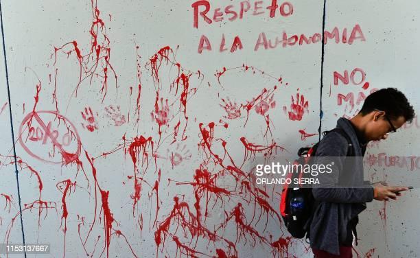 TOPSHOT A student of the National Autonomous University of Honduras checks his phone during a demonstration to demand Honduran President Juan Orlando...