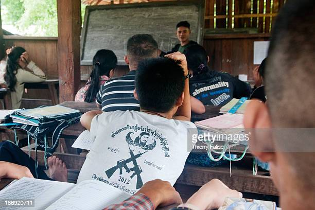 A student of the New Generation School a preuniversity school set up in the jungle by the Karen National Union wears a tshirt bearing the effigy of...