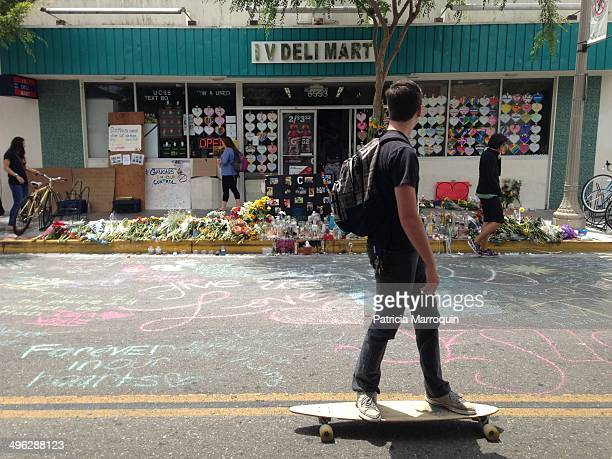 A UCSB student on a skateboard looks at the makeshift memorial set up in front of the IV Deli Mart in Isla Vista California where USB student...