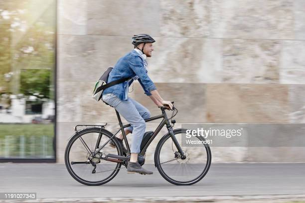 student on his e-bike at goethe university in frankfurt, germany - radfahren stock-fotos und bilder