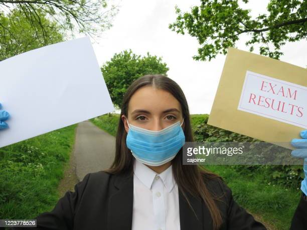 student opening exam results after lockdown - blue blazer stock pictures, royalty-free photos & images