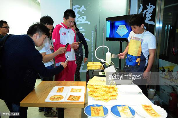 A student operates a 3D printer to print various types of pancakes which attracts crowd's photographing on April 19 2016 in Beijing China The 3D...