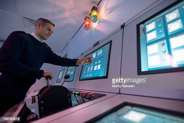 Student operating equipment in ship's engine room simulator