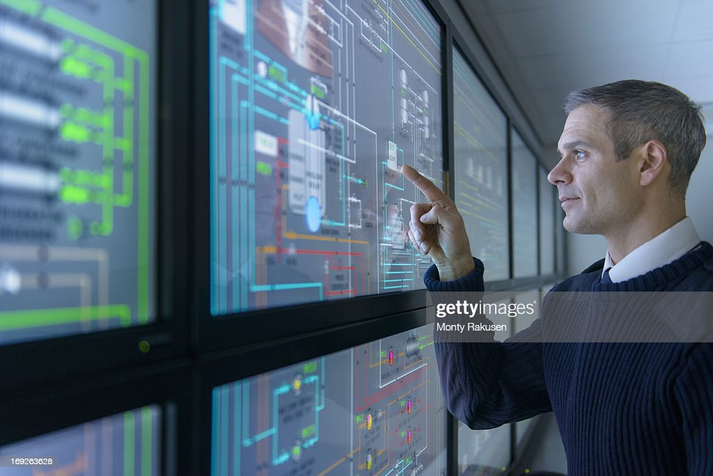 Student operating equipment in ship's engine room simulator : Stock Photo