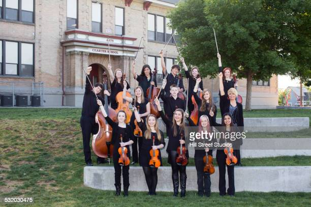 Student orchestra posing together outside high school