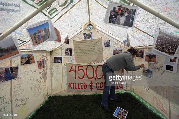 A student organizer hangs pictures taken at refugee camps in the African nation of Chad inside the 'Darfur' tent during the Genocide Awareness fair...