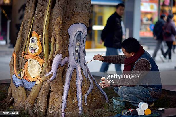 A student paints cartoon animal drawings on the tree trunk at a pedestrian street on January 5 2016 in Chongqing China Students from art school...
