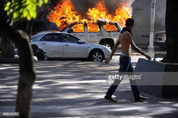 A student passes by burnt CICPC cars during a demontration against the government of Venezuelan President Nicolas Maduro in Caracas on February 12...
