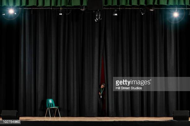 student peering from behind curtain on stage - backstage stock pictures, royalty-free photos & images