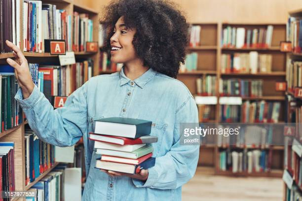 図書館で本を選ぶ学生 - 自己改善 ストックフォトと画像