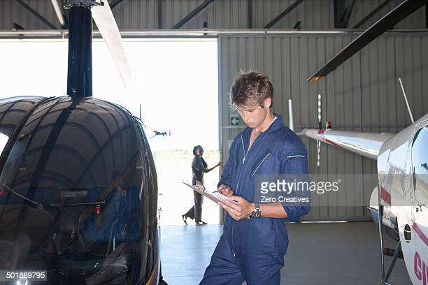 student pilot checking details on clipboard - white jumpsuit stock photos and pictures